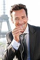 Businessman using a hands_free device with the Eiffel Tower in the background, Paris, Ile_de_France, France