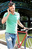 Man walking with a bicycle and talking on a mobile phone, Paris, Ile_de_France, France