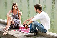 Couple drinking red wine at the ledge of a canal, Paris, Ile_de_France, France