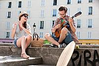 Man playing a guitar with a woman clapping and smiling, Canal St Martin, Paris, Ile_de_France, France