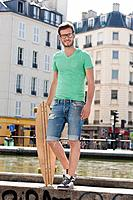 Man standing on the ledge of a canal with a skateboard, Canal St Martin, Paris, Ile_de_France, France