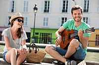 Man playing a guitar with a woman smiling, Canal St Martin, Paris, Ile_de_France, France