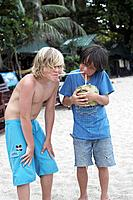 Two boys 8_10 years drinking fresh coconut milk, Haad Thong Reng, Island of Ko Pha Ngan, Surat Thani, Thailand