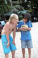 Two boys 8_10 years drinking fresh coconut milk, Haad Thong Reng, Island of Ko Pha Ngan, Surat Thani, Thailand