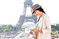 Woman reading a guide book with the Eiffel Tower in the background, Paris, Ile_de_France, France
