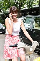 Woman riding a bicycle and talking on a mobile phone, Paris, Ile_de_France, France