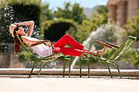 Woman resting in a chair near a pond, Bassin octogonal, Jardin des Tuileries, Paris, Ile_de_France, France