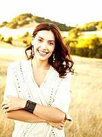 Beautiful happy woman walking in nature wearing a long sweater laughing