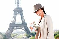 Woman holding a postcard with the Eiffel Tower in the background, Paris, Ile_de_France, France