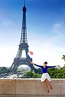 Woman holding a French flag sitting on a stone wall with the Eiffel Tower in the background, Paris, Ile_de_France, France