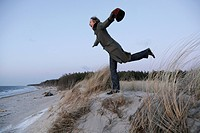 Woman balancing on one food in dunes, Baltic sea spa Ahrenshoop, Mecklenburg_Western Pomerania, Germany