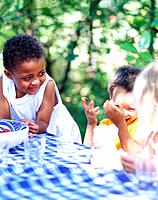 Three Children Playing at Table in Garden
