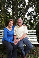 Senior Hispanic couple sitting on park bench