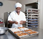 Mixed race baker icing pastry in commercial kitchen