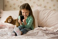 Caucasian girl sitting on bed text messaging on cell phone