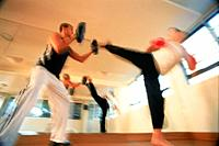 Two men kickboxing at gymnasium