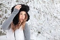 Young woman with cap in snow