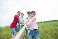Four children playing tug_of_war