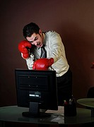 Young Businessman with boxing gloves attacking computer