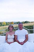 Senior Couple Resting on Bed in Field