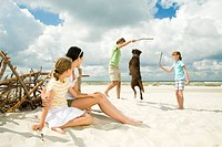 family on beach playing with dog