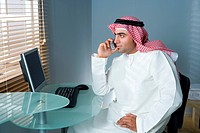 Arab man with cellphone in the office