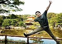 Young Man Jumping in Front of Kinkaku_Ji Temple Temple of the Golden Pavilion, Kyoto, Japan