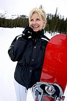 Female Senior with Snowboard Using Mobile Phone