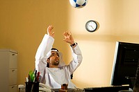 Arab man playing football in office
