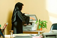 Young businesswoman using photocopier