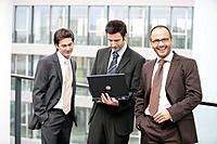 Three Business Men Standing with Laptop in Front of Window in Office Hall