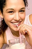Young Woman Drinking a Glass of Milk with a Straw