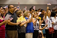Immigrants of many ages and nationalities cheer and wave U S  flags after taking the oath of United States citizenship in Los Angeles