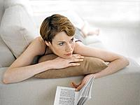 Woman Lying on Couch Holding Book