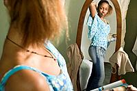 Young Woman Admiring Herself in Mirror
