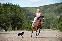 Cowgirl handling horse and riding on horseback
