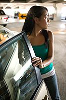Cautious Young Woman Getting into Car in Parking Garage