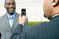 Businessman Taking Picture with Cell Phone