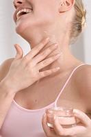 woman applying cream on neck