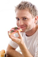 man eating sandwich with salami