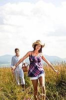 young couple with picnic basket walking through field