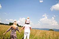 rear view of young family walking through meadow