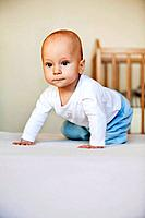 portrait of young baby boy crouching on floor