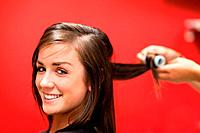 Smiling woman having her hair rolled with a curler