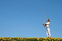 Girl playing berimbau in spring meadow