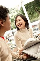 Smiling Couple Reading Newspaper Outside