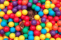Little Boy Hiding Under Bunch of Balls
