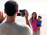 Father Videotaping Family at Beach