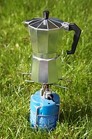 gourmet coffee percolator precariously balanced on a gas camping stove