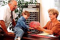 Grandpa helping grandson deposit his savings